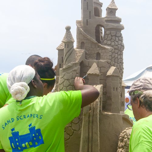 Amateur team working on sand sculpture
