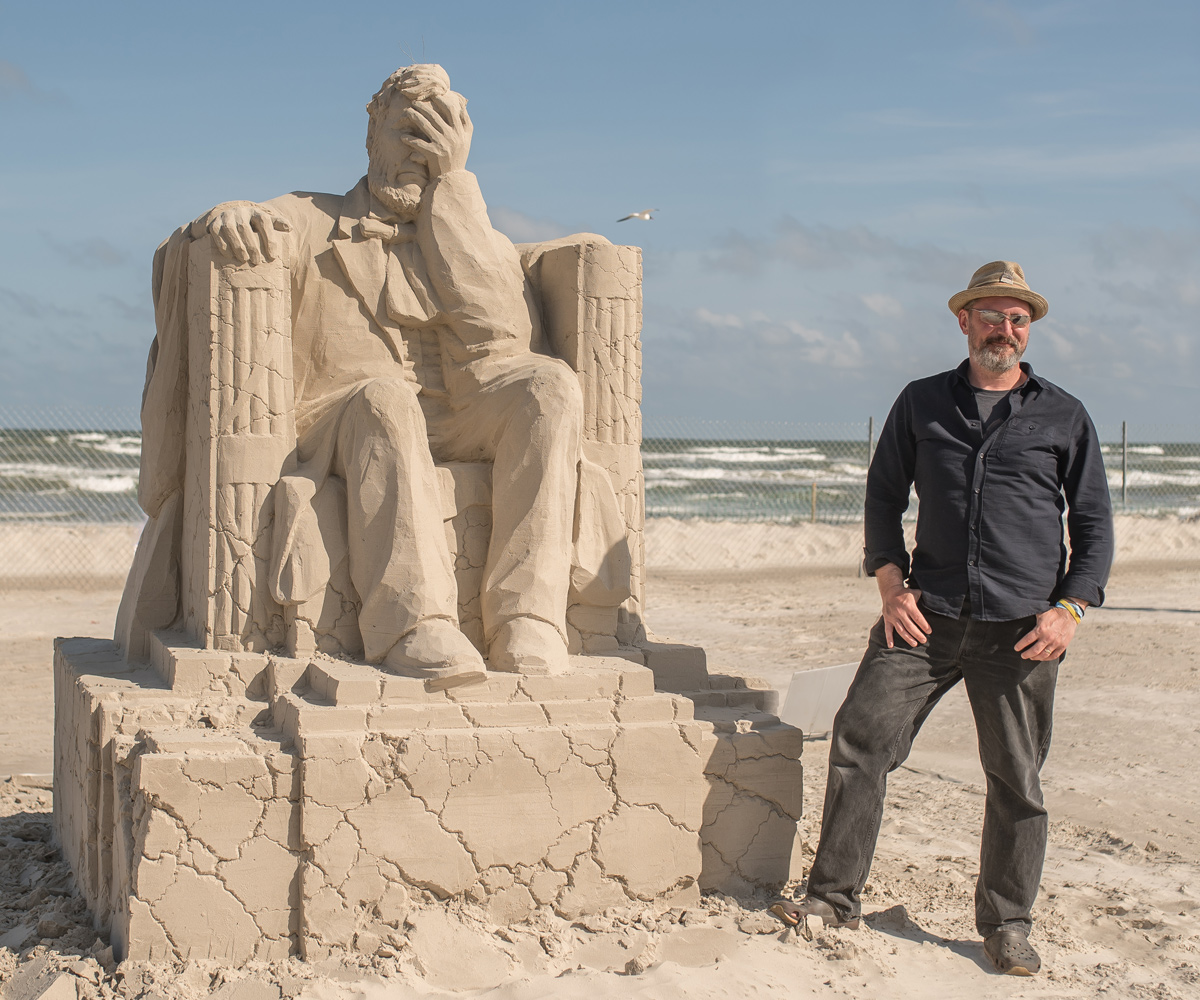 Sand sculpture of Abraham Lincoln, covering his face with his hand