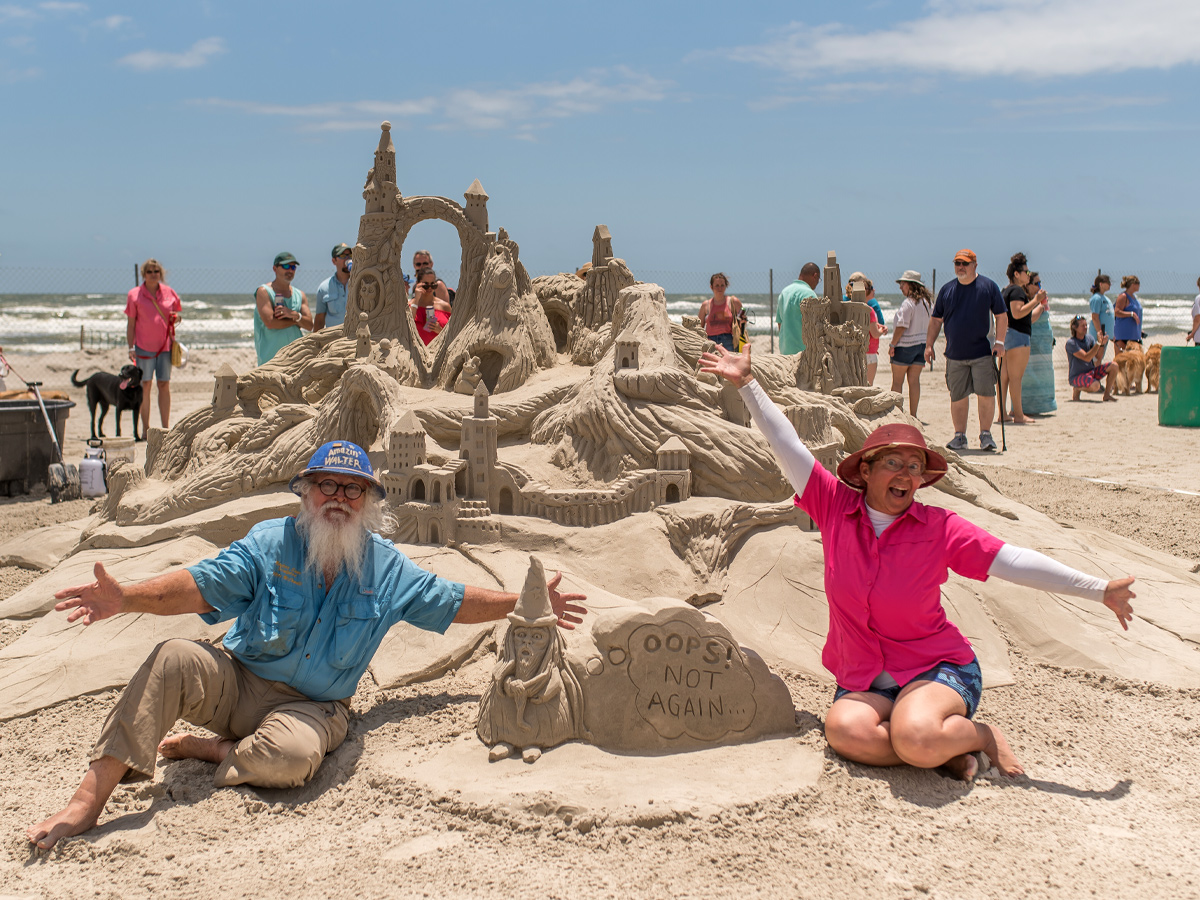 Walter and Christy pose in front of a sculpture of a large intricate sand castle.